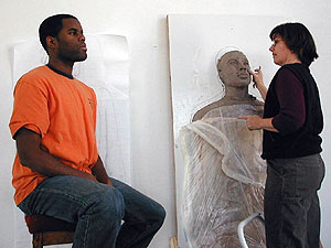 Delon Grant posing while artist Carla Stetson does finecarving work on the figure for the memorial.  (MPR photo/Bob Kelleher)
